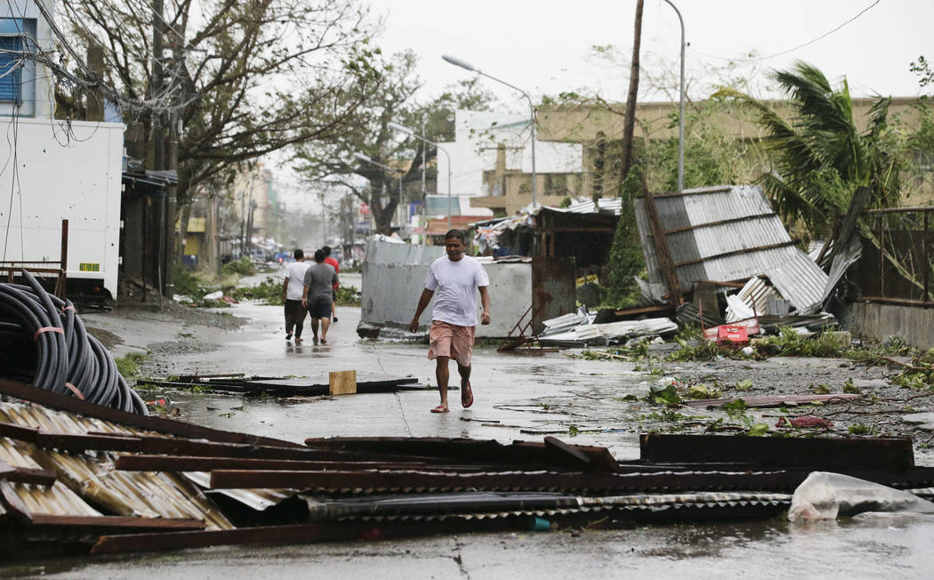 FILE - In this Saturday, Sept. 15, 2018, file photo, a resident walks beside toppled structures as Typhoon Mangkhut barreled across Tuguegarao city in Cagayan province, northeastern Philippines. ( ...