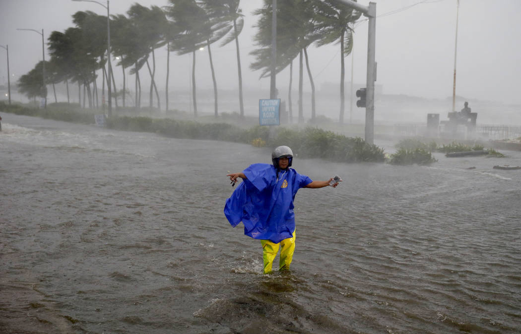 FILE - In this Saturday, Sept. 15, 2018, file photo, a man directs traffic to avoid a flooded street at the onslaught of Typhoon Mangkhut which barreled into the northeastern Philippines before da ...