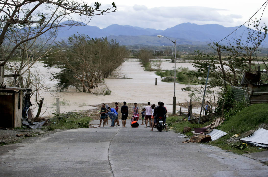 FILE - In this Saturday, Sept. 15, 2018, photo, residents stand by a flooded road following the onslaught of Typhoon Mangkhut in Tuguegarao City in Cagayan province, northeastern Philippines. (AP ...