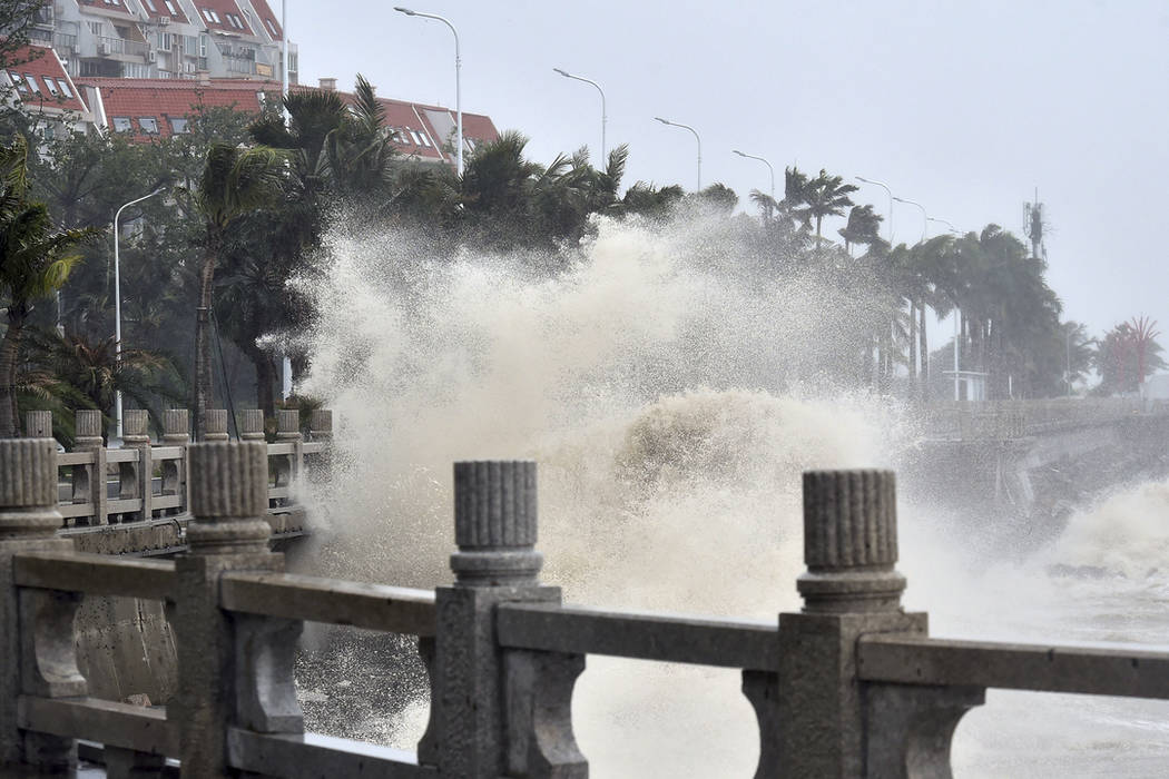 In this photo released by Xinhua News Agency, waves crash onto the coastline in Zhuhai in southern China's Guangdong Province on Sunday, Sept. 16, 2018. (Liang Xu/Xinhua via AP)