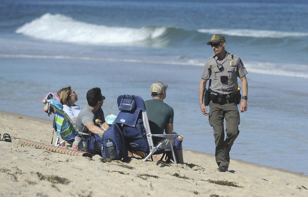 Cape Cod National Seashore Park Ranger Eric Trudeau walks up to a group of visitors on Newcomb Hollow Beach telling them that the beach is closed to swimming, Saturday, Sept. 15, 2018, in Wellflee ...