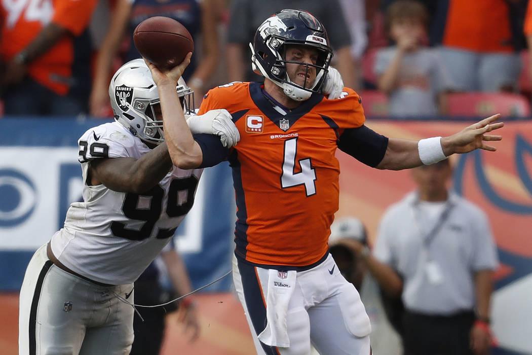 Denver Broncos quarterback Case Keenum (4) is pressured by Oakland Raiders defensive end Arden Key (99) during the second half of an NFL football game, Sunday, Sept. 16, 2018, in Denver. The Bronc ...