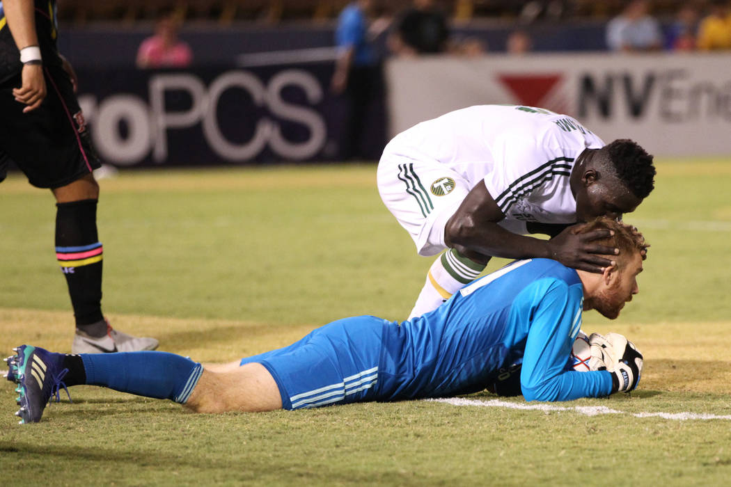 Portland Timbers' Modou Jadama (26), top, embraces goalkeeper Alex Mangels (41) after making a key stop agains the Las Vegas Lights at Cashman Field in Las Vegas, Sunday, Sept. 16, 2018.The ...