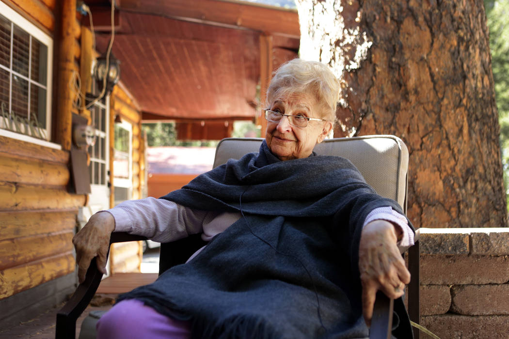 Rose Meranto sits in front of the stump of a Ponderosa pine that was estimated to be 100-feet-tall and 300-years-old and growing next to her Mount Charleston until she was forced to to cut the dyi ...