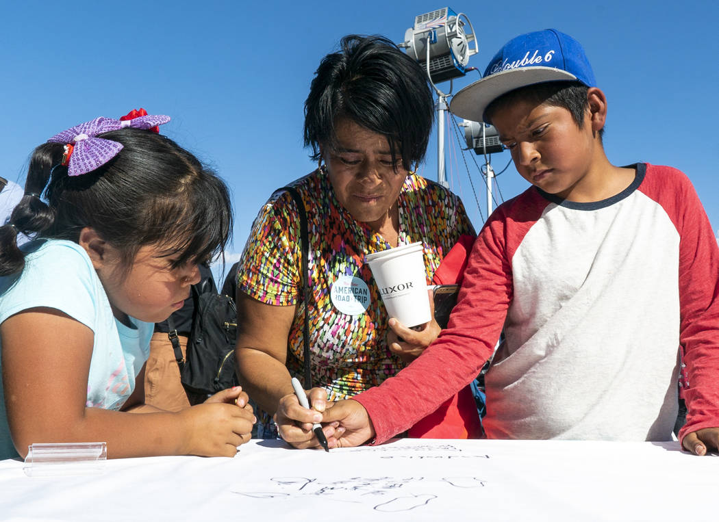 """From left, Ruby Estrada, 5, Ivan Meneses and Angel Meneses, 10, attend """"The New American Road Trip"""" stop in front of the Luxor casino-hotel in Las Vegas and sign a petition advocating fo ..."""