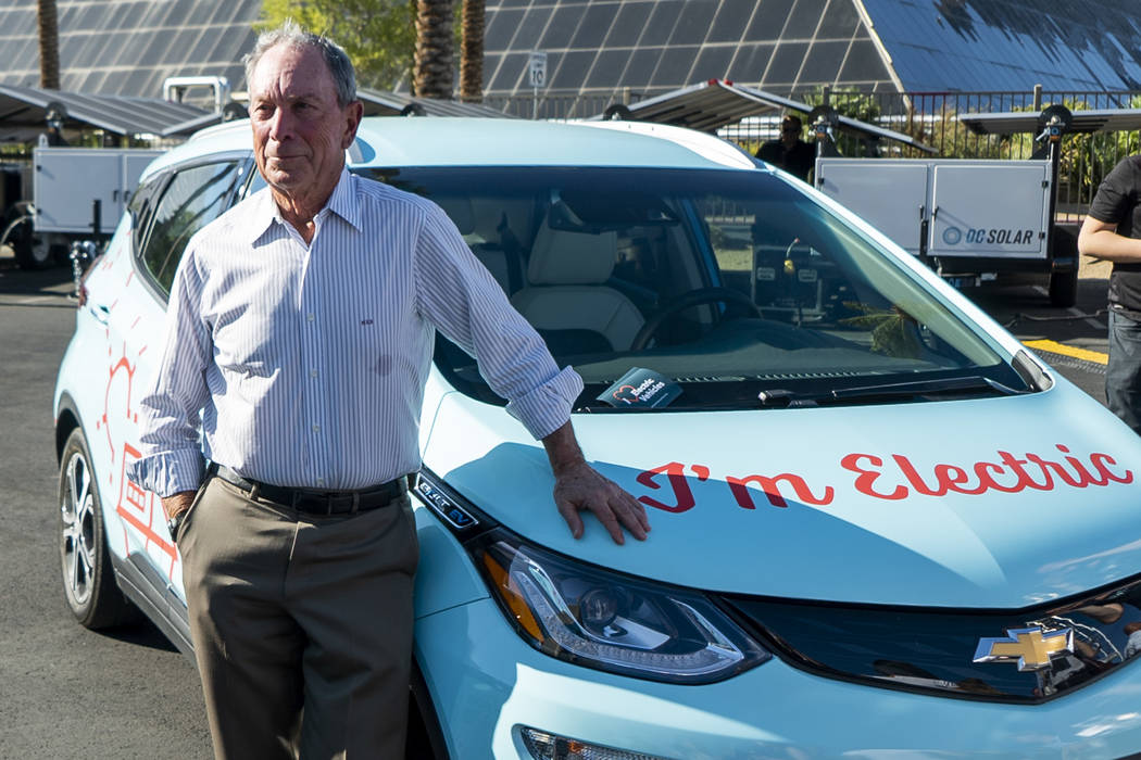"Former New York City mayor Michael Bloomberg poses for a photograph next to an electric vehicle in front of the Luxor casino-hotel in Las Vegas during ""The New American Road Trip,"" an el ..."