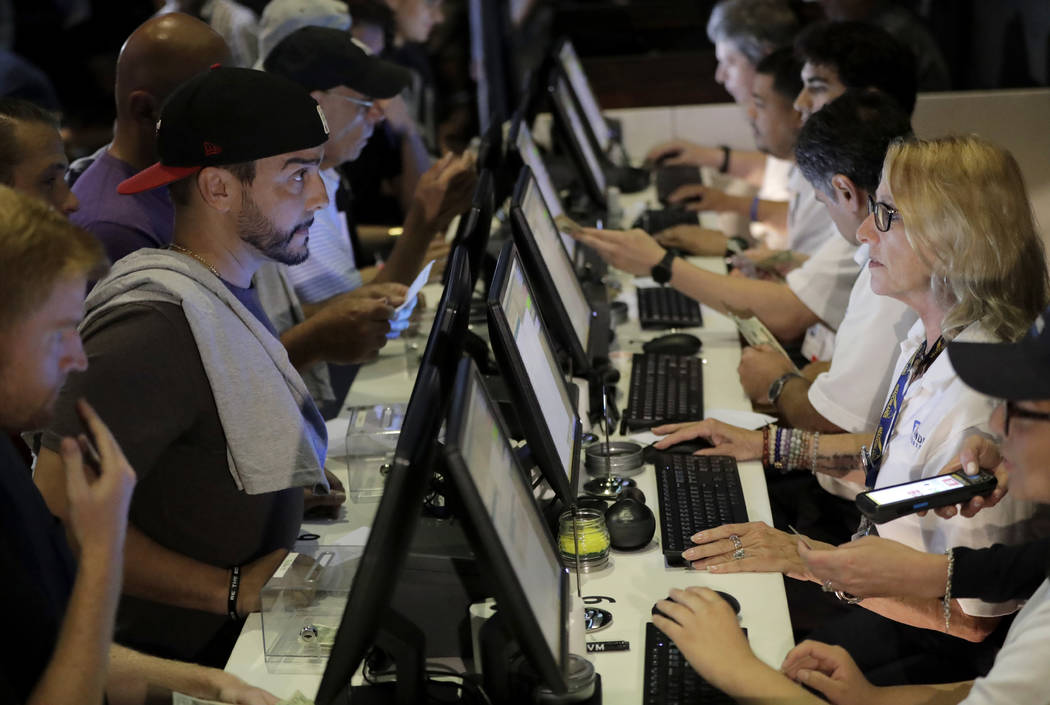In this July 14, 2018, file photo, people, left, talk to tellers while placing bets at the Meadowlands Racetrack, in East Rutherford, N.J. (AP Photo/Julio Cortez, File)