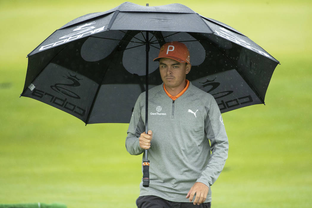 Rickie Fowler looks on while under an umbrella during the BMW Championship golf tournament at the Aronimink Golf Club, Monday, Sept. 10, 2018, in Newtown Square, Pa. Keegan Bradley held off Justin ...