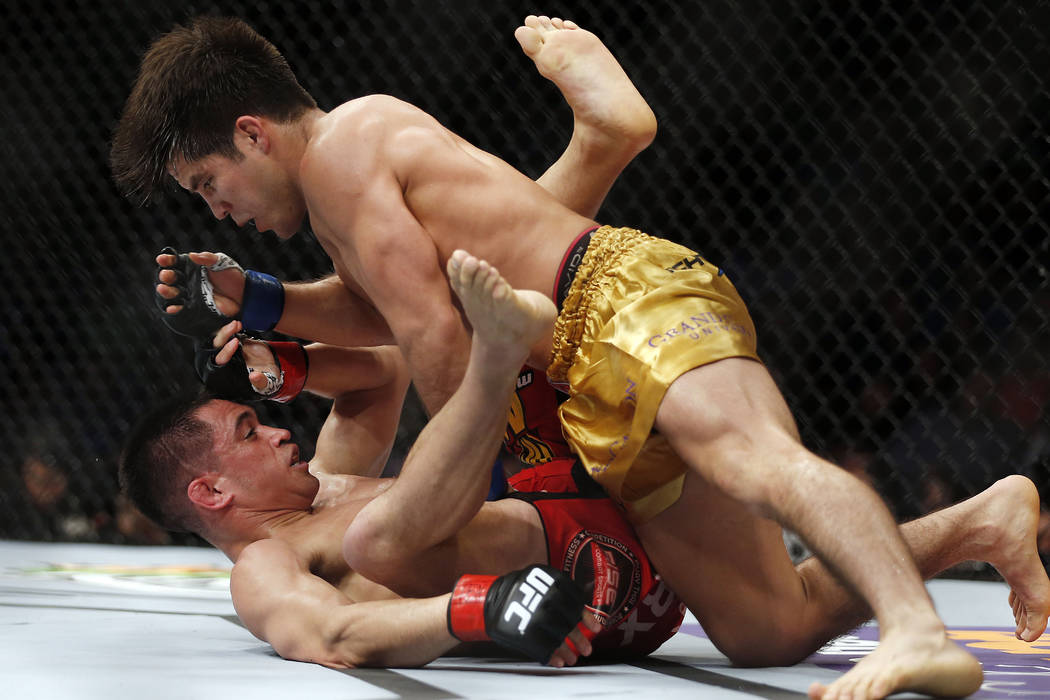 Henry Cejudo, top, forces Chris Cariaso to the mat during a men's flyweight UFC 185 mixed martial arts bout, Saturday, March 14, 2015, in Dallas. Cejudo won the match in three rounds. (AP Photo/Br ...