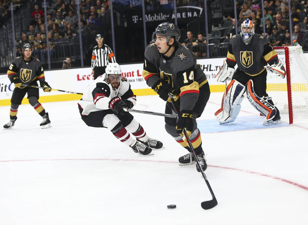 Golden Knights defenseman Nicolas Hague (14) moves the puck against the Arizona Coyotes during the second period of a preseason NHL hockey game at T-Mobile Arena in Las Vegas on Sunday, Sept. 16, ...