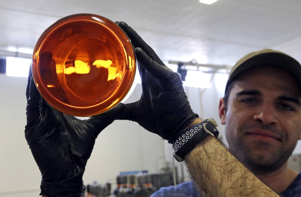 FILE--In this April 24, 2018, file photo, Julian Cabrera, factory manager at New Earth Biosciences, holds up a large glass beaker containing thick, golden-colored, fully-refined CBD oil in Salem, ...