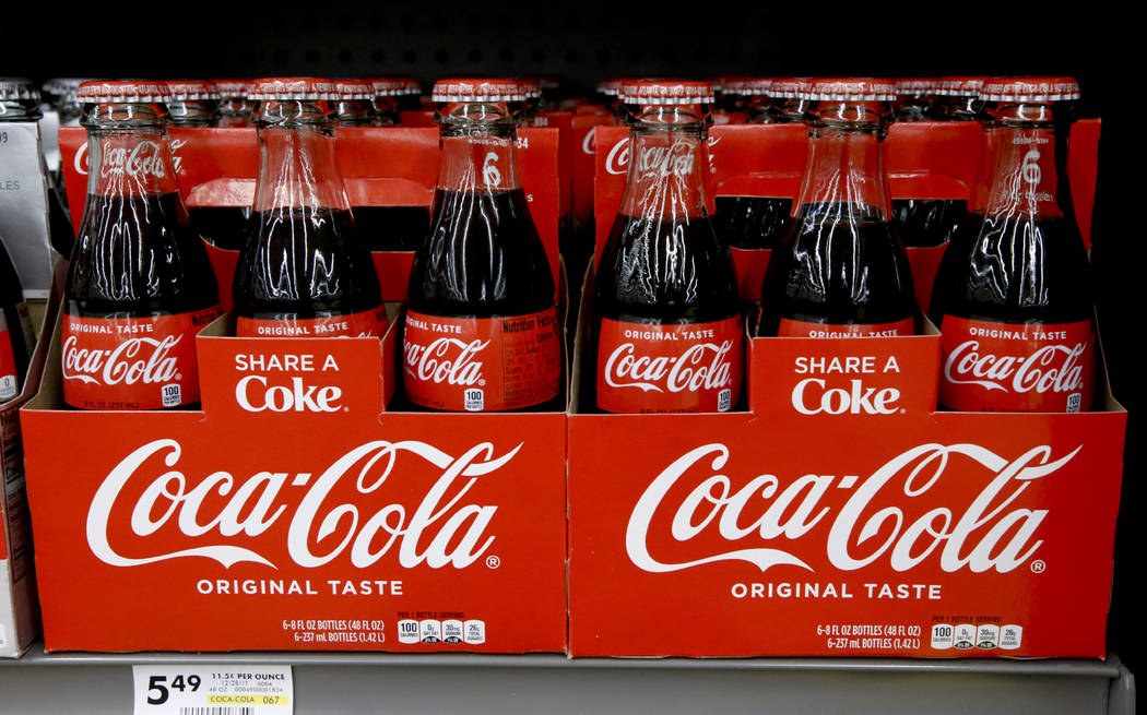 """FILE--In this Aug. 8, 2018, file photo, bottles of Coca Cola sit on a shelf in a market in Pittsburgh. The Coca-Cola Company says that it's """"closely watching"""" the growth of the use of a ..."""