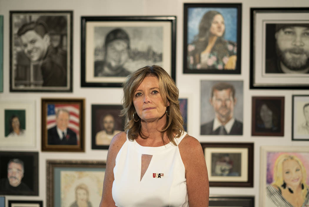 Mary Jo von Tillow, wife of Kurt von Tillow, a victim from the Route 91 festival shooting, poses for a photograph in front of the Las Vegas Portraits Project at the Clark County Government Center ...