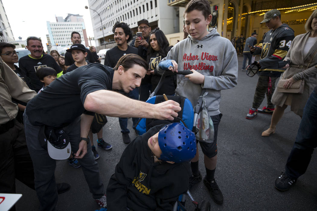 Vegas Golden Knights goaltender Marc-Andre Fleury signs the helmet of Las Vegas resident Tyler Calarco, 16, during the team's first fan fest at the Fremont Street Experience in downtown Las Vegas ...