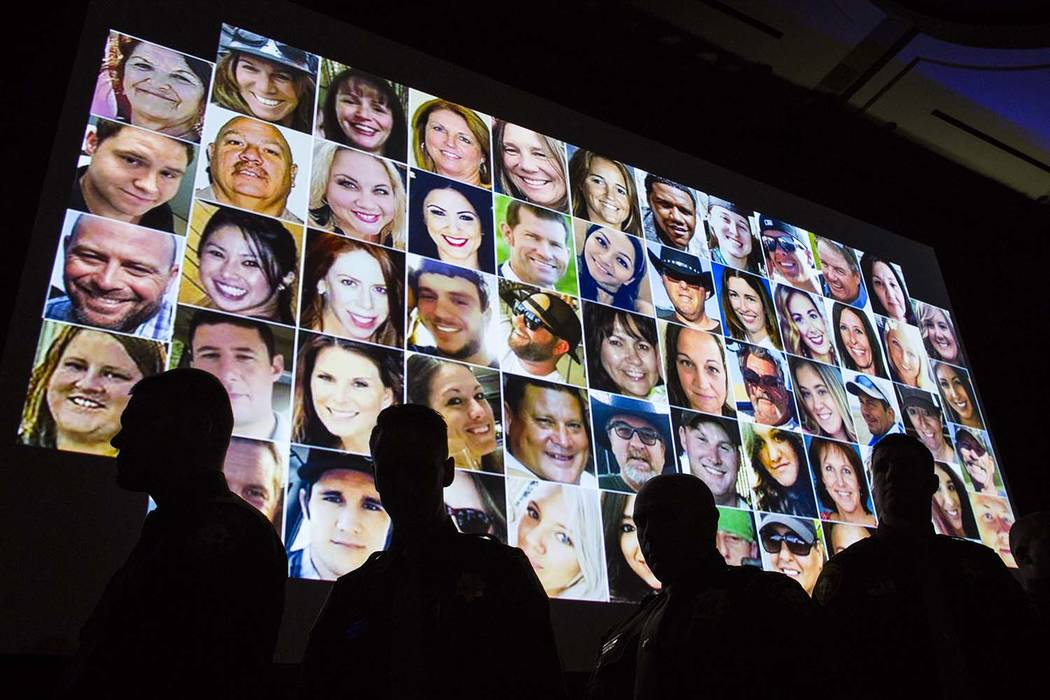 Las Vegas police officers are silhouette during 58 seconds of silence in memory of the victims of the Oct. 1 attack, displayed above, during the Best of the Badge gala held by the Metropolitan Pol ...