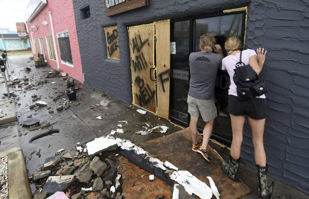 In this Monday, Sept. 17, 2018 photo, Crush & Grind owners Brett Gurkin, left, and Nadine Antonelli look into their business along the Carolina Beach Boardwalk in Carolina Beach, N.C. The busi ...