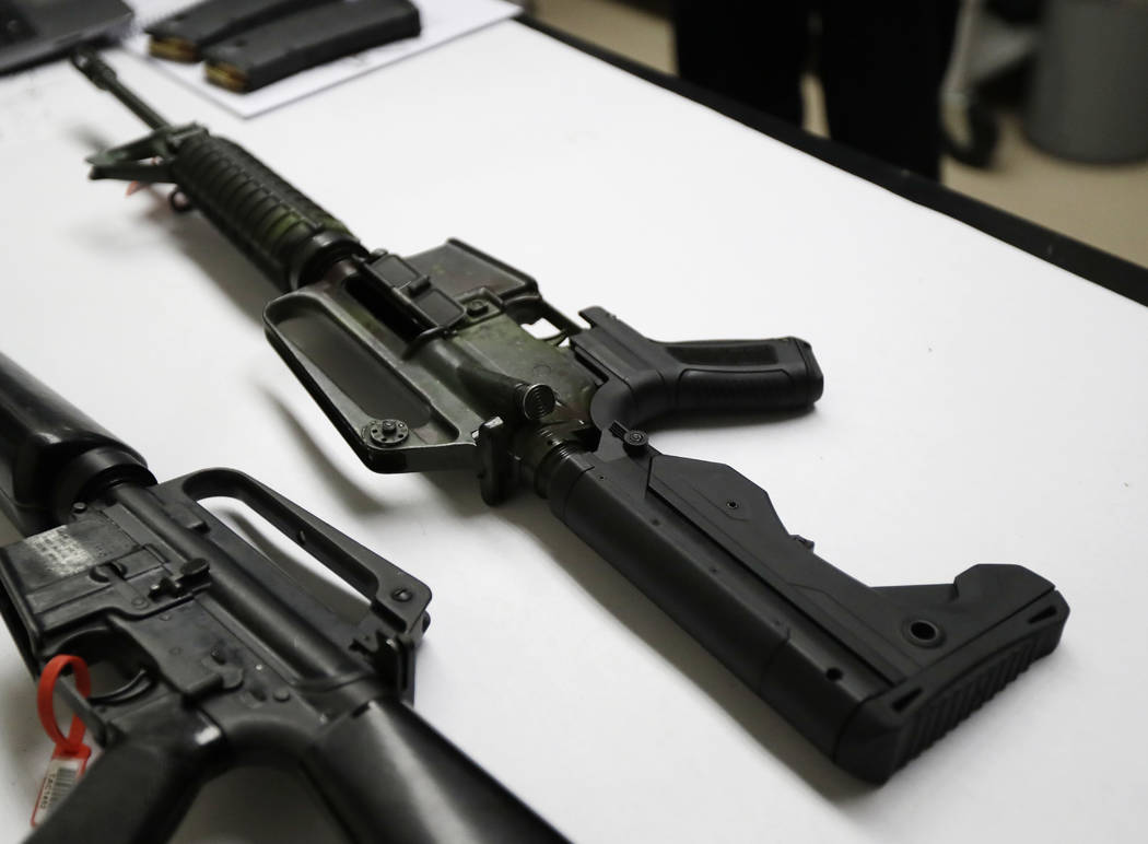A semi-automatic rifle that has been fitted with a so-called bump stock device to make it fire faster sits on a table at the Washington State Patrol crime laboratory in Seattle on Jan. 11, 2018. ...