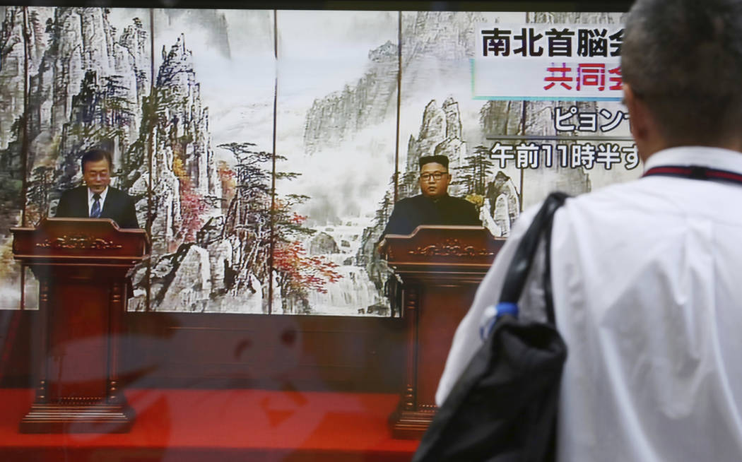 A man watches a TV screen showing a joint news conference by North Korean leader Kim Jong Un and South Korean President Moon Jae-in, left, in Pyongyang, North Korea, on a news program in Tokyo, We ...