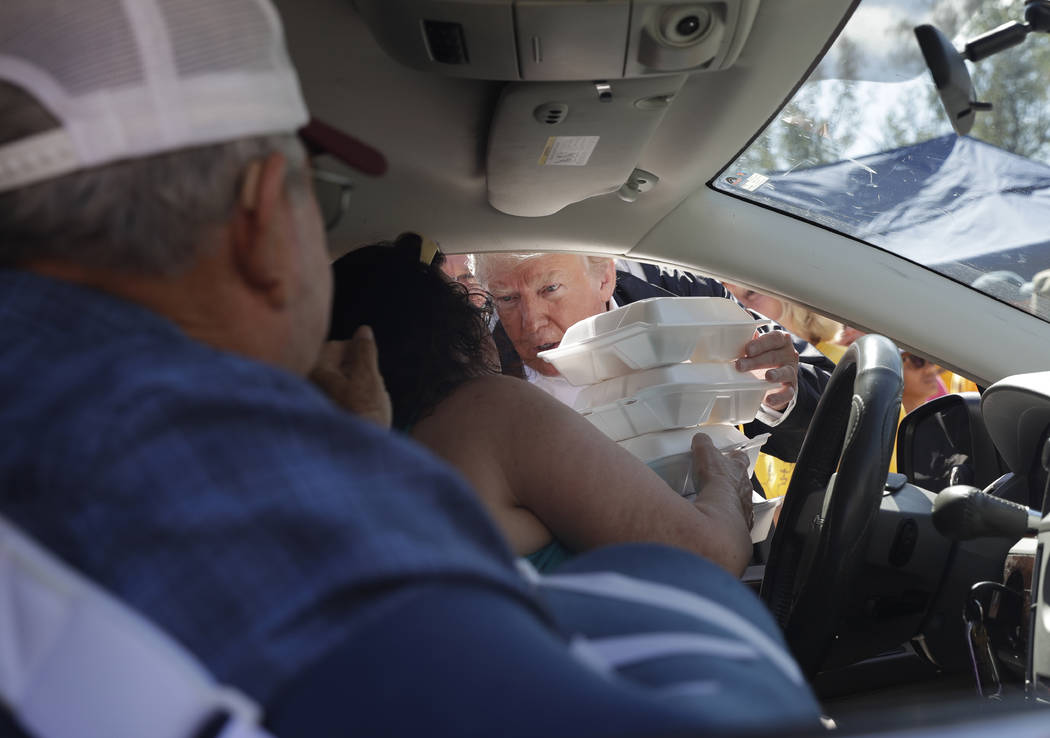 President Donald Trump hands out food at Temple Baptist Church, where food and other supplies are being distributed during Hurricane Florence recovery efforts, Wednesday, Sept. 19, 2018, in New Be ...