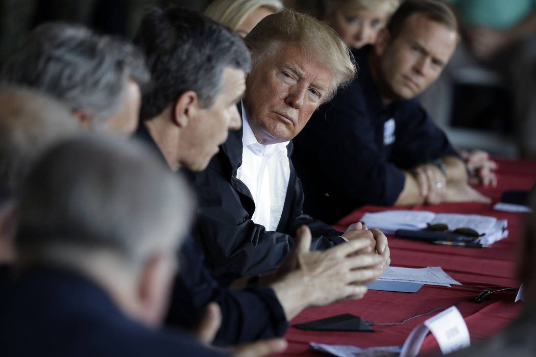 President Donald Trump listens as North Carolina Gov. Roy Cooper speaks while attending a briefing, after arriving at Marine Corps Air Station Cherry Point to visit areas impacted by Hurricane Flo ...