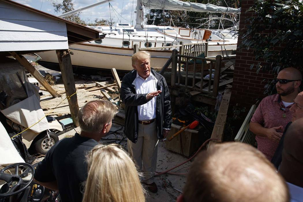 President Donald Trump visits a neighborhood impacted by Hurricane Florence, Wednesday, Sept. 19, 2018, in New Bern, N.C. (AP Photo/Evan Vucci)