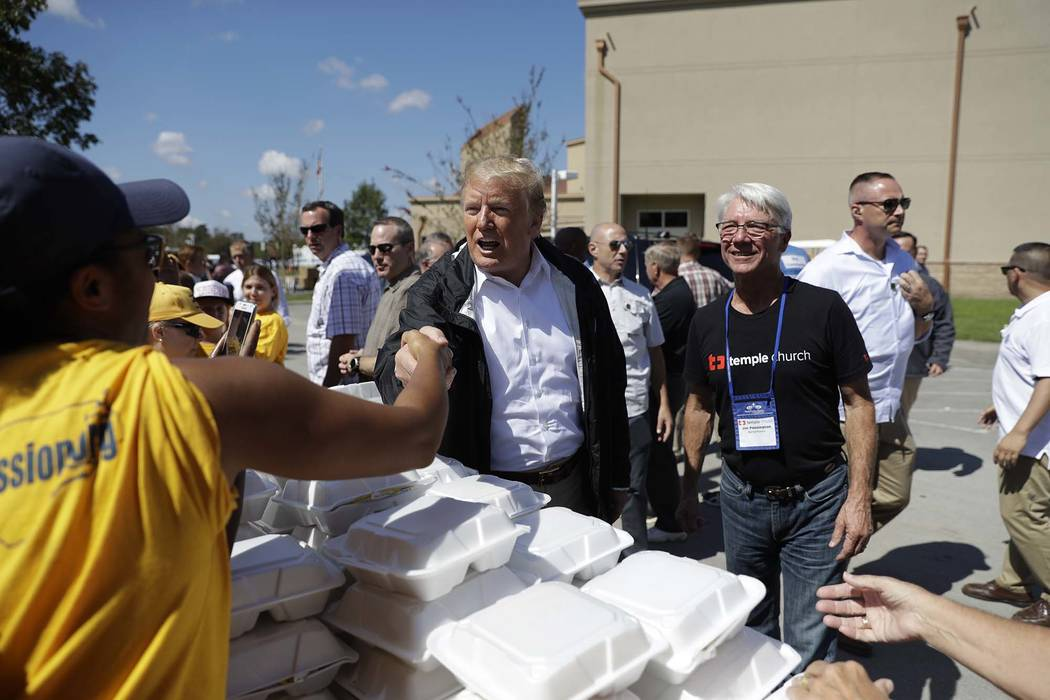 President Donald Trump visits the Temple Baptist Church, where food and other supplies are being distributed during Hurricane Florence recovery efforts, Wednesday, Sept. 19, 2018, in New Bern, N.C ...