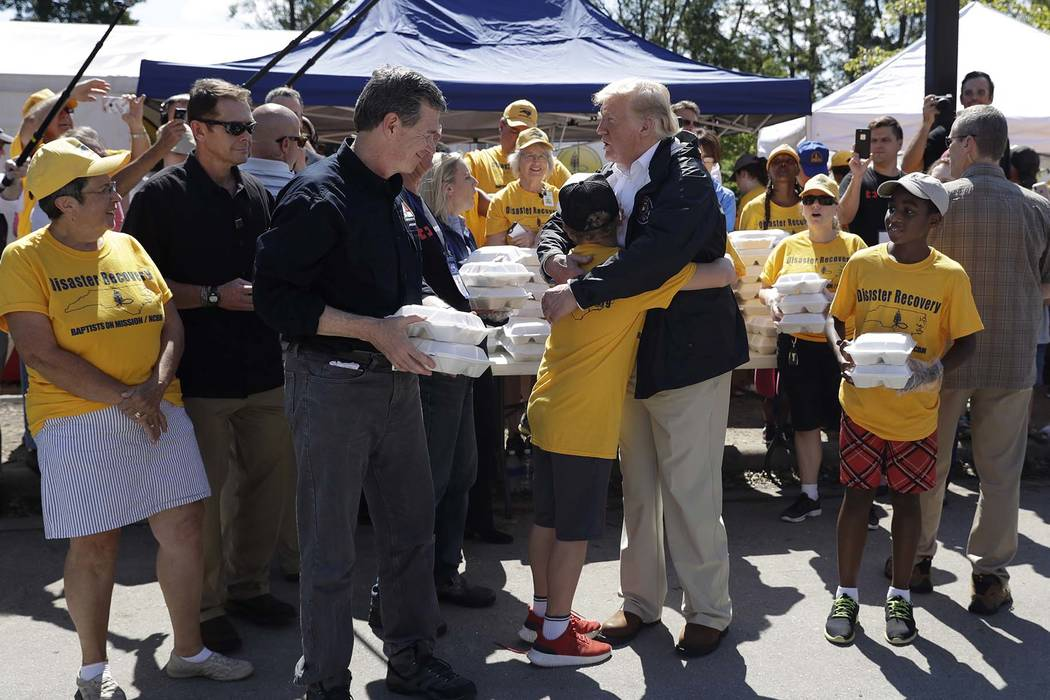 President Donald Trump and North Carolina Gov. Roy Cooper, left, greet volunteers as they prepare to hand out food at Temple Baptist Church, where food and other supplies are being distributed dur ...