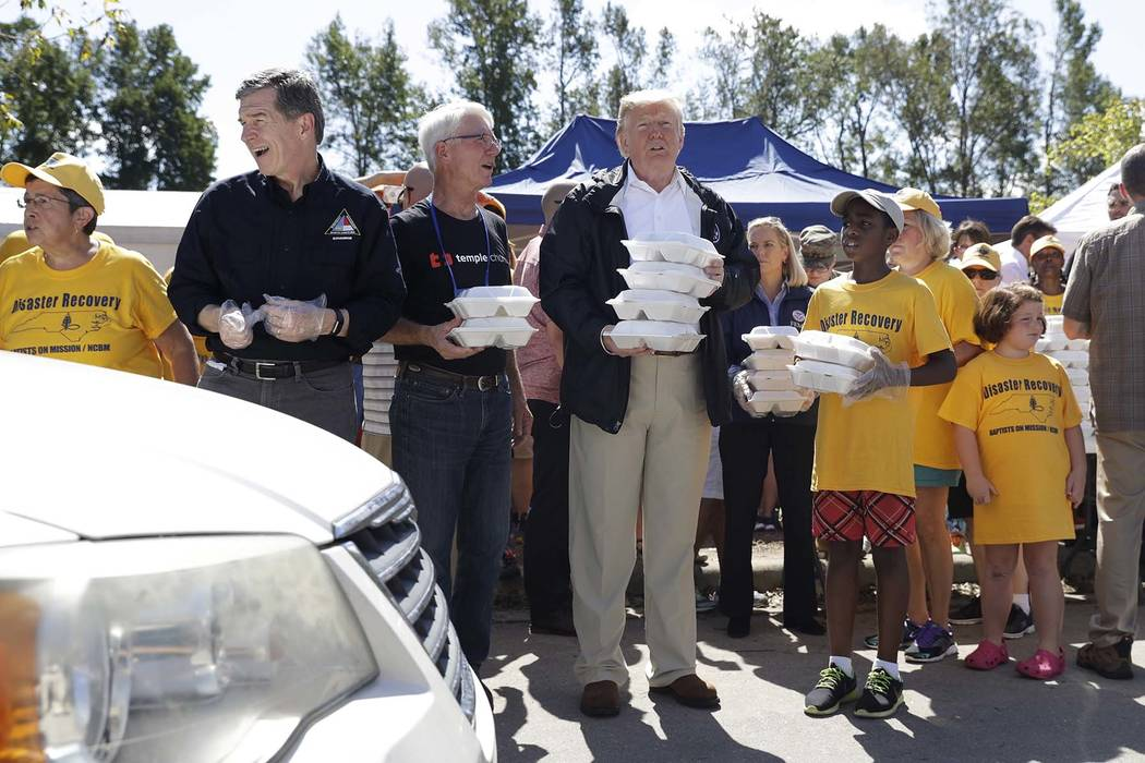 As cars drive up, President Donald Trump, North Carolina Gov. Roy Cooper, left, and volunteers, hand out food at Temple Baptist Church, where food and other supplies are being distributed during H ...