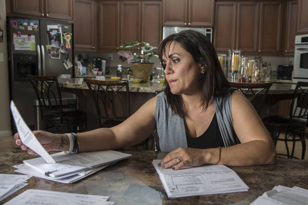 Rose Janise looks through her daughter Rylie Golgart's medical bills she accrued after being shot in the back during the Route 91 shooting on Thursday, Sept. 20, 2018, at Janise's home, in Henders ...