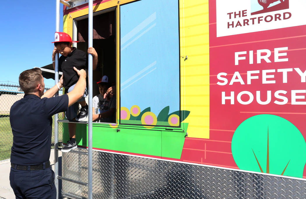 Armando Cendejas is assisted by a Clark County firefighter as he practices escaping through a window during a fire prevention and safety event at Ann T Lynch Elementary School on Thursday, Sept. 2 ...