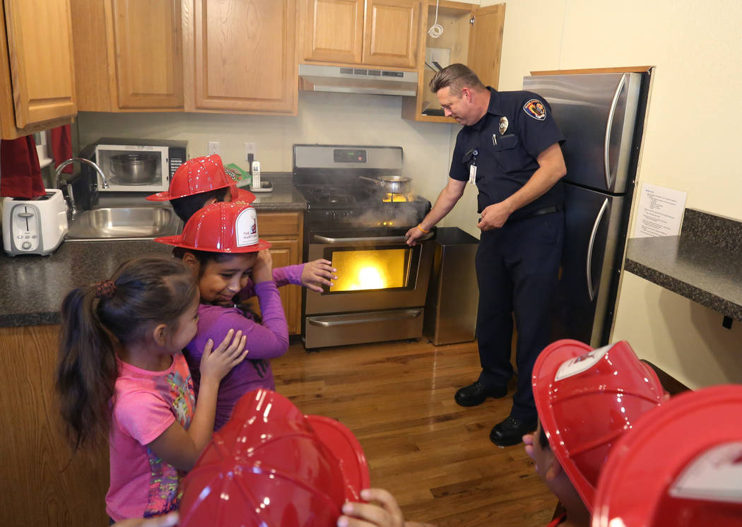 Clark County firefighter Steven Dieter demonstrates how to extinguish a grease fire to second grade students during a fire prevention and safety event at Ann T Lynch Elementary School on Thursday, ...