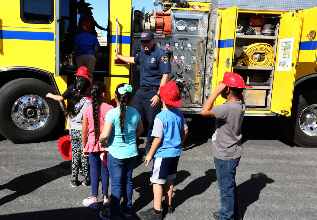Clark County firefighter Matthew Teasley watches as second grade students lined up to check out a fire truck during a fire prevention and safety event at Ann T Lynch Elementary School on Thursday, ...