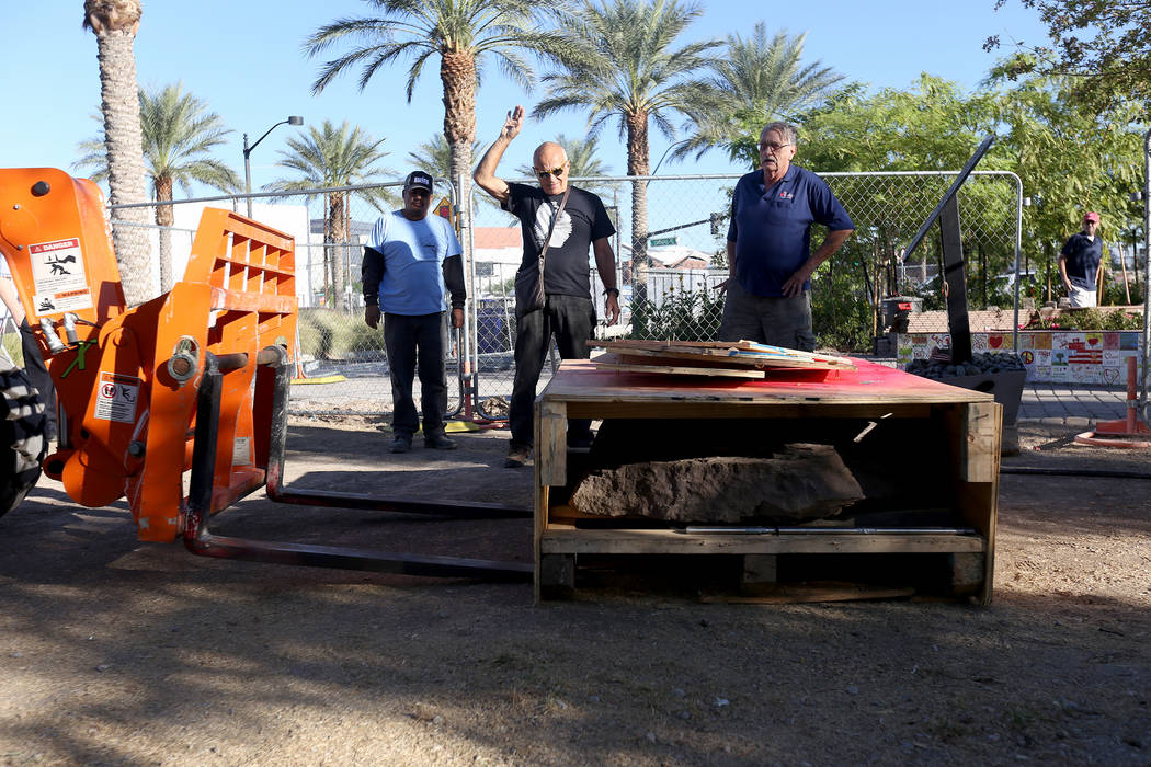 Jose Cernes, from left, artist Bobby Jacobs, center, and David Schember, oversee the moving of the base of a stone sculpture designed by Jacobs to the Healing Garden in Las Vegas, Thursday, Sept. ...