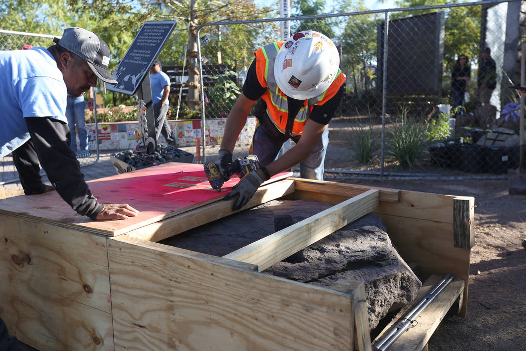 Jose Cernes, left, and Jon Serfilippi pull out the screws to reveal the base of the stone sculpture designed by artist Bobby Jacobs that will be placed in the Healing Garden in Las Vegas, Thursday ...