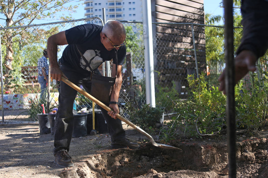 Artist Bobby Jacobs digs a deeper pit for the installation of a stone sculpture he created in the Healing Garden in Las Vegas, Thursday, Sept. 20, 2018. The back of the wings of the sculpture have ...