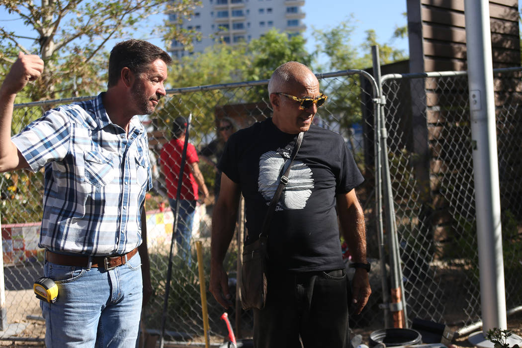 Jay Pleggenkuhle, left, owner of Stone Rose Landscapes who operate the Healing Garden, speaks to artist Bobby Jacobs as they oversee the installation of a stone sculpture designed by Jacobs at the ...