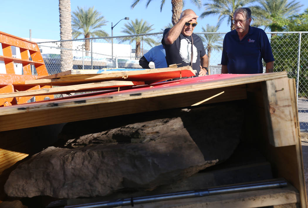 Artist Bobby Jacobs, left, and David Schember, right, oversee the installation of a stone sculpture he created in the Healing Garden in Las Vegas, Thursday, Sept. 20, 2018. The back of the wings o ...