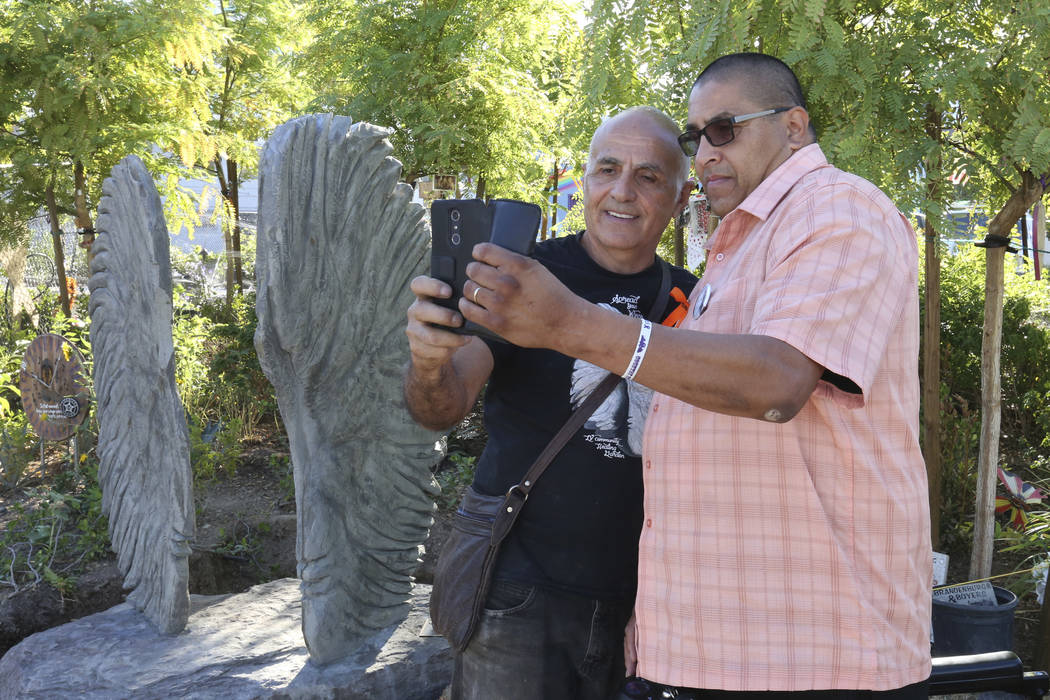 Bobby Jacobs, left, an artist from upstate New York, and Daniel Rosales, a survivor of the Oct. 1 shooting, take a selfie next to a sculpture, left, of two separate angel wings at the Las Vegas He ...