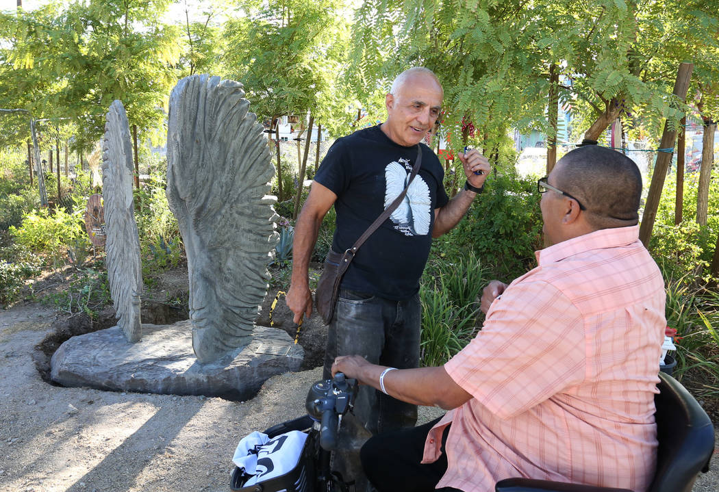 Bobby Jacobs, left, an artist from upstate New York, chats with Daniel Rosales, a survivor of the Oct. 1 shooting, next to his sculpture, left, of two separate angel wings at the Las Vegas Healing ...