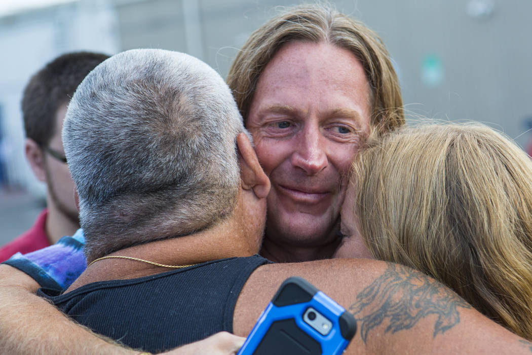Timothy Tyler, center, embraces his cousin, Dave Phelps, left, and friend Hilary after visiting a halfway house to remove his ankle monitor at the completion of his sentence on Thursday, Aug. 30, ...