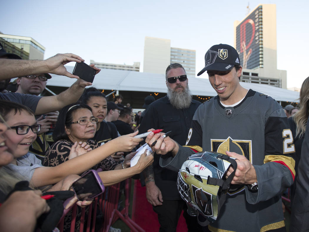 Vegas Golden Knights goaltender Marc-Andre Fleury (29), right, signs a helmet for Anthony Mora, left, during a Vegas Golden Knights fan fest at the Downtown Las Vegas Events Center on Wednesday, S ...