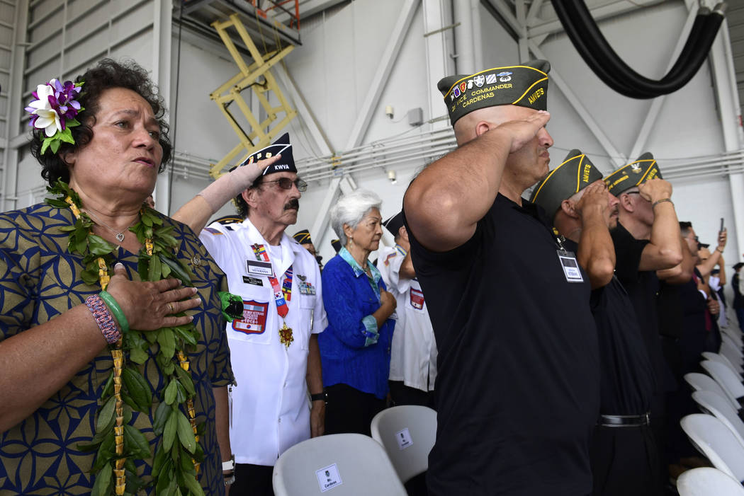 Audience members stand during the National Anthem at a ceremony marking the arrival of the remains believed to be of American service members who fell in the Korean War at Joint Base Pearl Harbor- ...