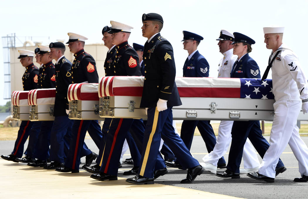 Military members carry transfer cases from a C-17 at a ceremony marking the arrival of the remains believed to be of American service members who fell in the Korean War at Joint Base Pearl Harbor- ...