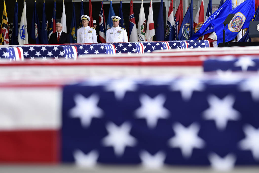 Vice President Mike Pence, Commander of U.S. Indo-Pacific Command Adm. Phil Davidson, center, and Rear Adm. Jon Kreitz, deputy director of the POW/MIA Accounting Agency, look at transfer cases at ...