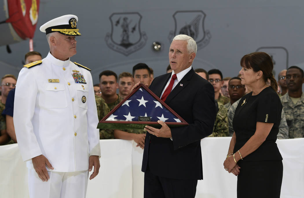 Vice President Mike Pence, center, receives a flag from Navy Rear Adm. Jon Kreitz, deputy director of the POW/MIA Accounting Agency, left, during a visit to Joint Base Pearl Harbor-Hickam in Hawai ...