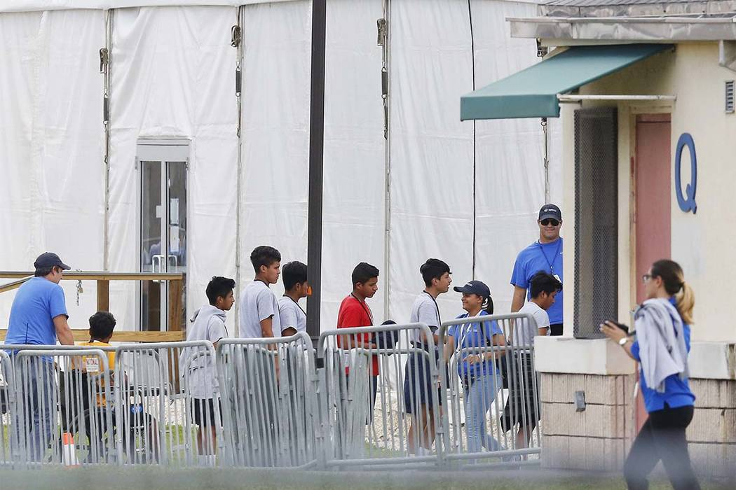 In this June 20, 2018, file photo, immigrant children walk in a line outside the Homestead Temporary Shelter for Unaccompanied Children a former Job Corps site that now houses them in Homestead, F ...