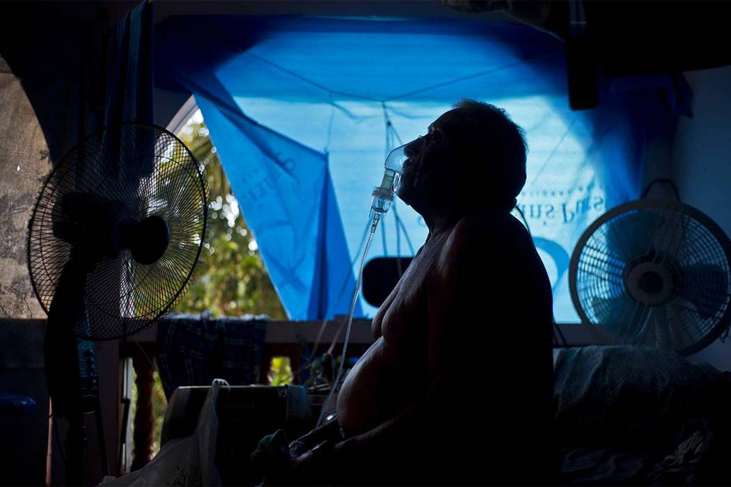 Gilberto Cosme Rodriguez takes one of his 10-a-day asthma treatments to help him breathe, inside his home still covered with a tarp after FEMA assistance failed to cover the cost of fixing his roo ...