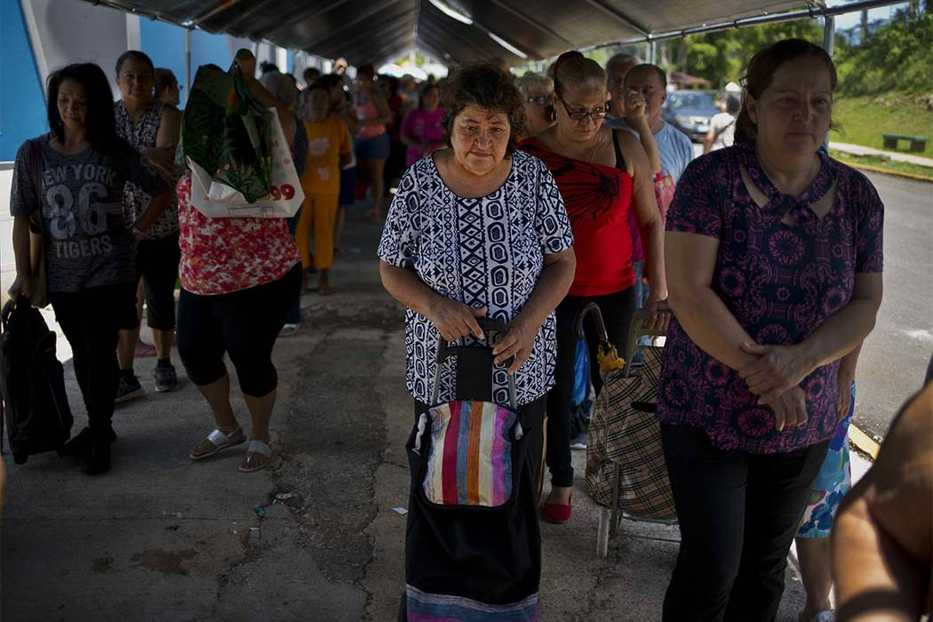 Elia de Jesus Acebedo waits in line for donated food and other basic goods from the MARC Ministry, a nonprofit charity in Manati, Puerto Rico. Acebedo, 67, said she and her sister rented a home th ...
