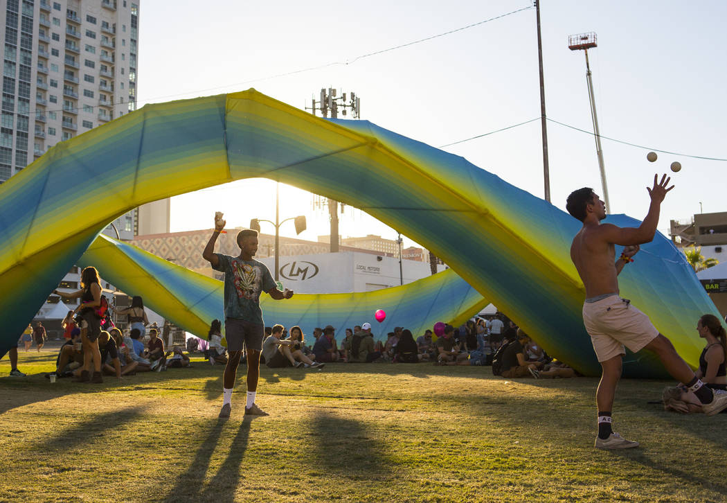 Eliud Evans, left, and Derrick Lietz, both of Los Angeles, juggle near an art installation during the third day of the annual Life is Beautiful festival in downtown Las Vegas on Sunday, Sept. 23, ...