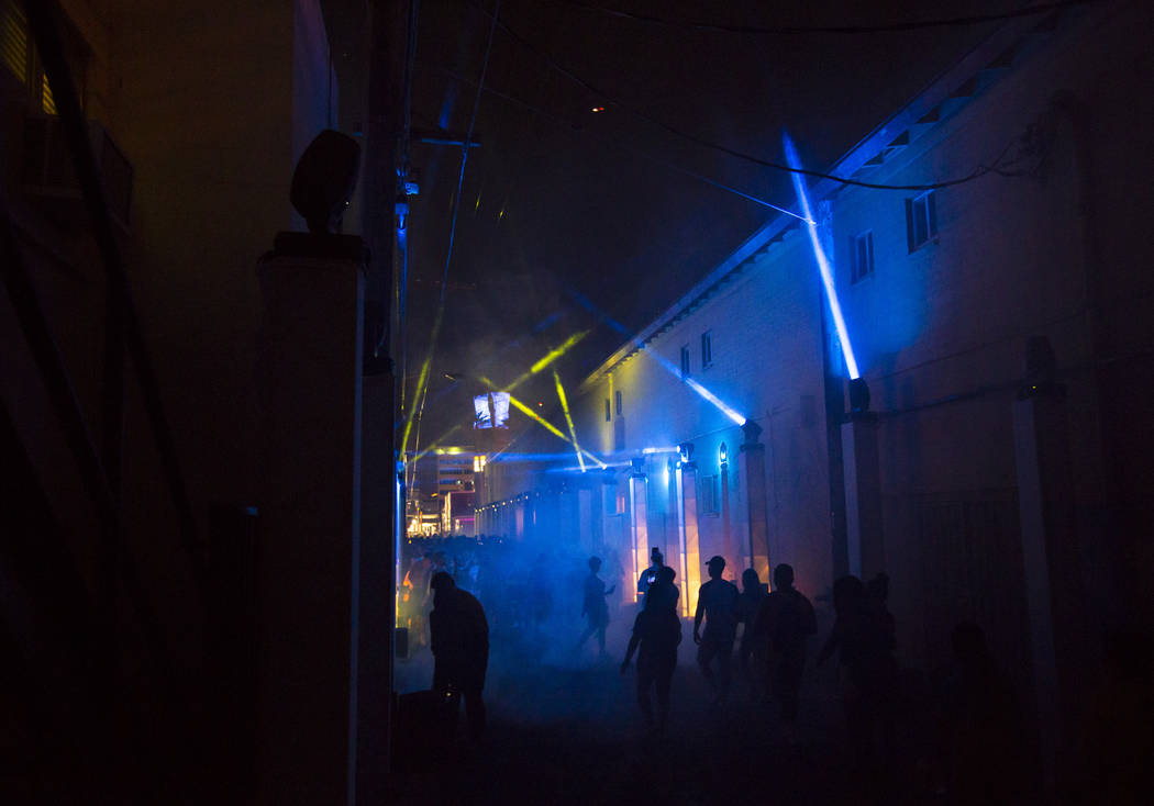 Attendees are silhouetted while walking through an alley during the third day of the annual Life is Beautiful festival in downtown Las Vegas on Sunday, Sept. 23, 2018. Chase Stevens Las Vegas Revi ...